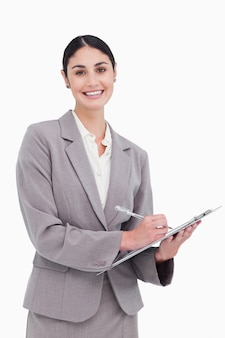 Smiling businesswoman ready to take notes against a white background