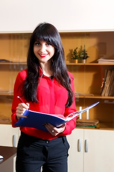 Smiling businesswoman in a red blouse with a folder of documents in the office