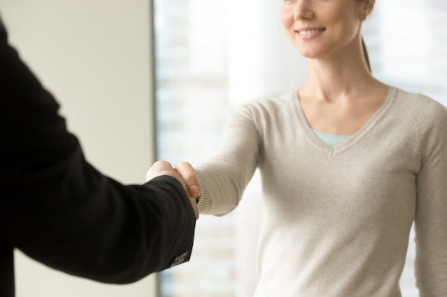 Smiling businesswoman shaking businessman hand in office