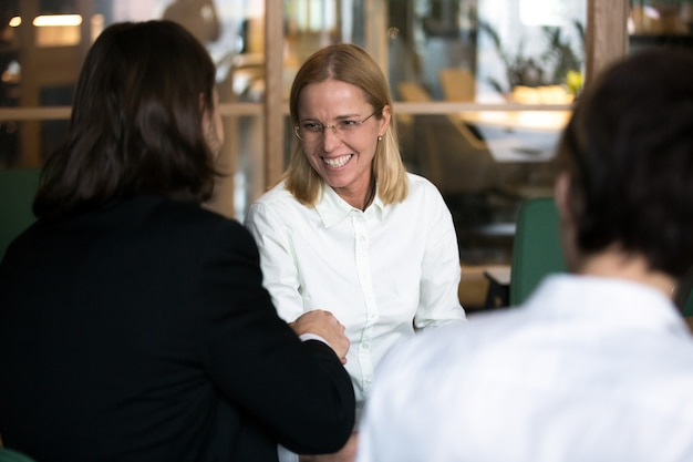 Smiling businesswoman shaking hand of businessman at negotiations or interview