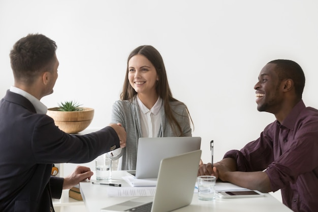 Smiling businesswoman shaking hand of male partner at group meeting