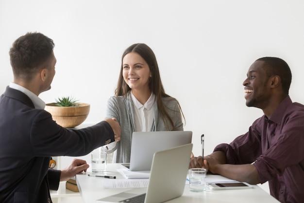 Улыбается бизнесвумен, пожимая руку мужского партнера на групповой встрече