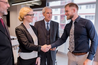 Smiling businesswoman shaking hand with businessman in the office