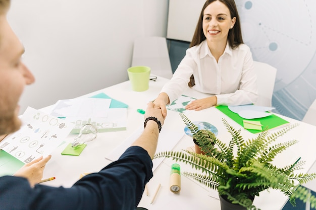 Smiling businesswoman shaking hands with her colleague in office