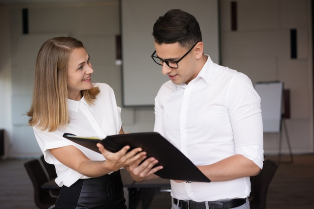 Smiling businesswoman showing folder with document to businessman.