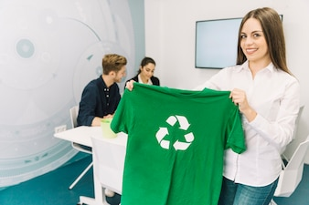 Smiling businesswoman showing green t-shirt with recycle symbol