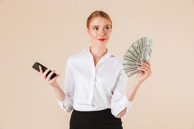 Улыбается бизнесвумен, показывая деньги
