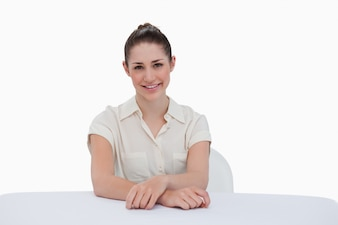 Smiling businesswoman sitting against a white background