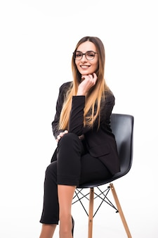 Smiling businesswoman sitting on a black chair on white