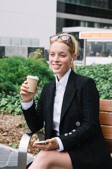 携帯電話と使い捨てのコーヒーカップを保持しているベンチに座っている笑顔の実業家