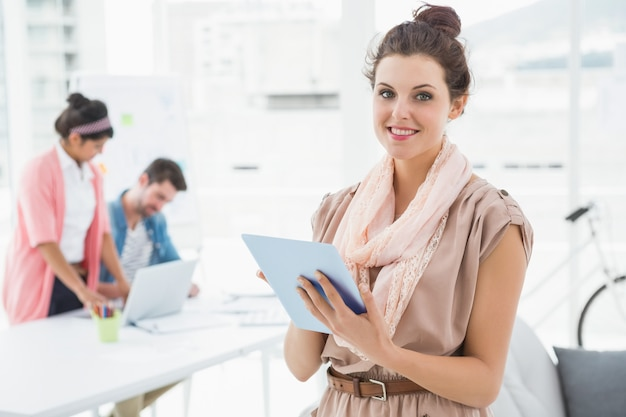 Smiling businesswoman standing and using tablet with colleagues behind her