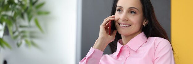Smiling businesswoman talking on phone in office.