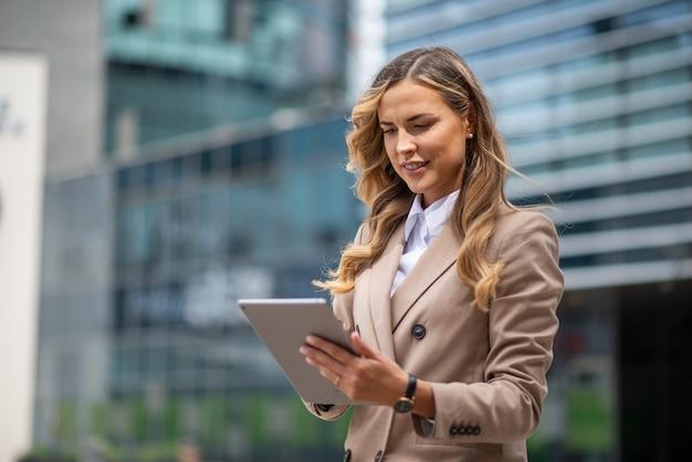 屋外でデジタルタブレットを使用して笑顔の実業家