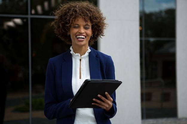 オフィスビルの近くでデジタルタブレットを使用して笑顔の実業家
