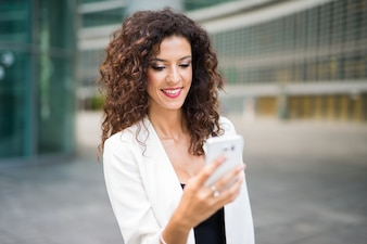 Smiling businesswoman using her mobile phone