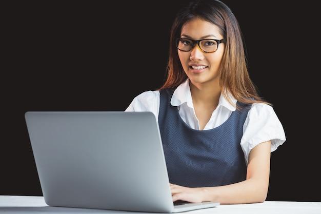 Smiling businesswoman using laptop on black background