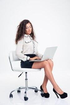 Улыбаясь бизнесвумен, используя ноутбук на офисном стуле