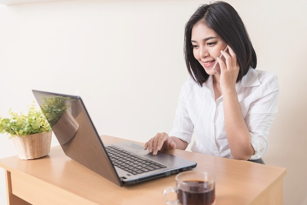 Smiling businesswoman using mobile phone at desk. success business. e-commerce.