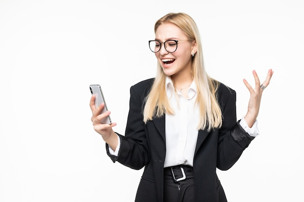 Smiling businesswoman using smartphone over gray wall.