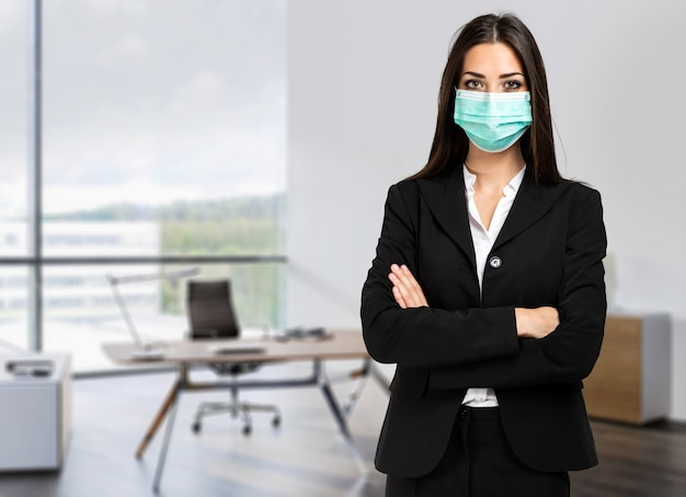Smiling businesswoman wearing a mask in her office, coronavirus concept