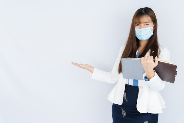 Smiling businesswoman wearing a medical face mask holding the notebook
