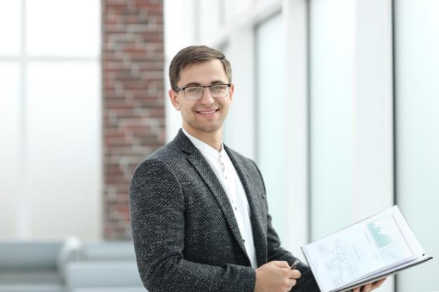 クリップボードがオフィスに立っている笑顔の実業家。ビジネスコンセプト