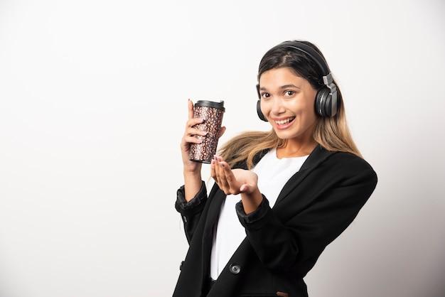Sorridente imprenditrice con tazza e cuffie.