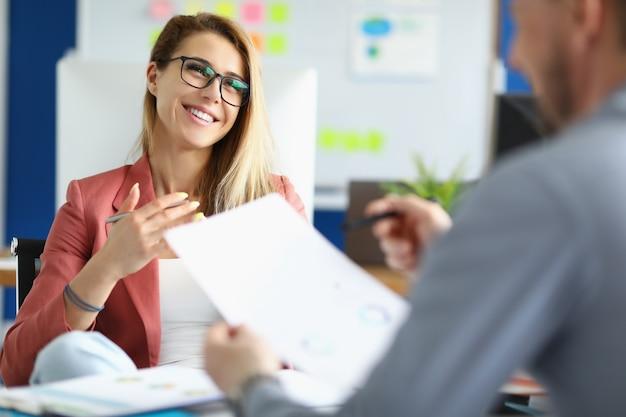 Улыбающаяся деловая женщина в очках общается с коллегой в офисе