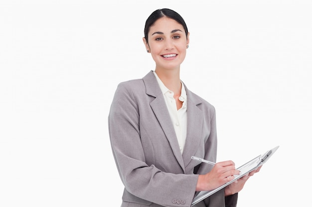 Smiling businesswoman with pen and clipboard