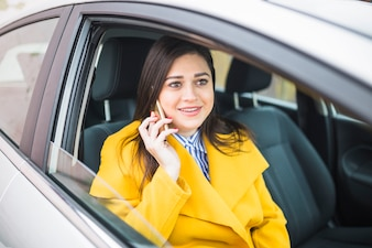 Smiling businesswoman with yellow coat sitting in car talking on smartphone