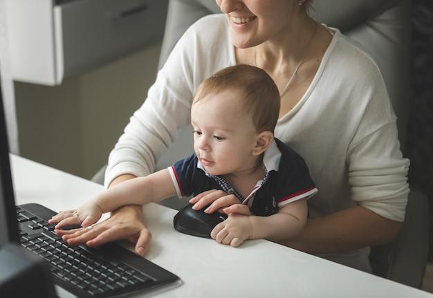 Улыбаясь бизнесвумен, работающая за компьютером с мальчиком, сидящим на ее коленях