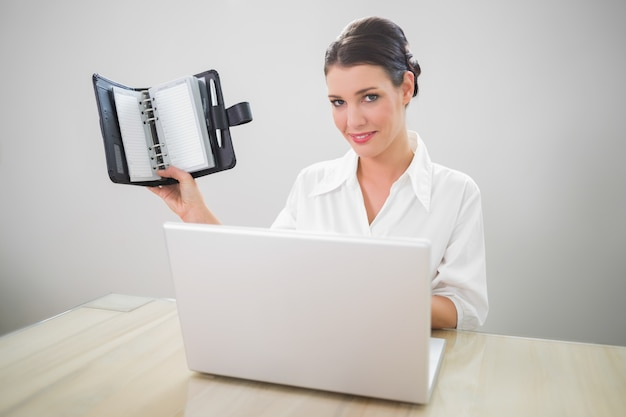 Smiling businesswoman working on laptop holding datebook