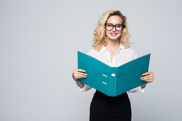 Smiling bussiness woman reading contracts from a folder isolated on white wall