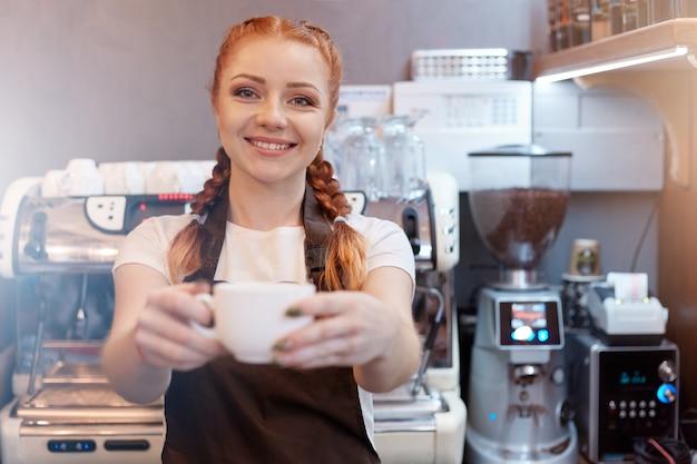 Улыбающаяся официантка в кафе предлагает чашку свежего кофе