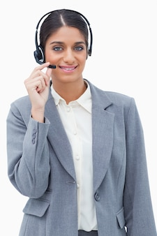 Smiling call center agent adjusting microphone