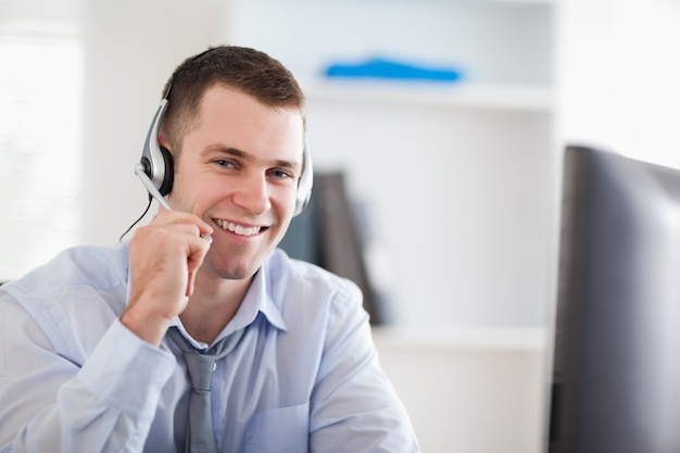 Smiling call center agent speaking with costumer