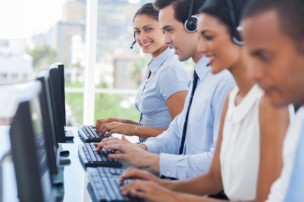 Smiling call centre employees working on computers