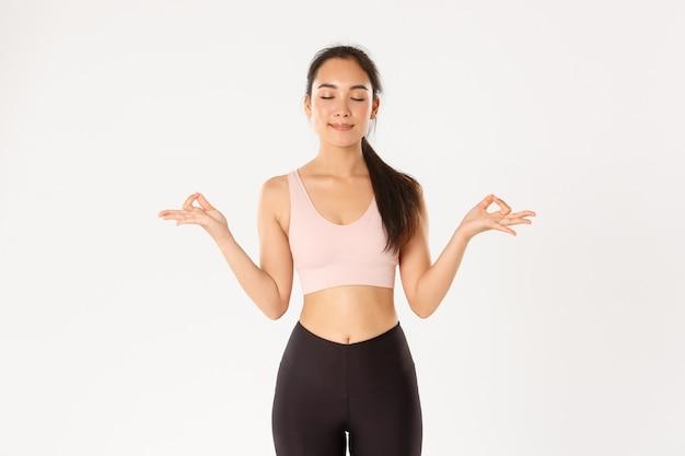 Улыбающаяся спокойная и расслабленная фитнес-девушка, женщина в спортивной одежде закрывает глаза и, стоя в позе лотоса, достигает нирваны на занятиях йогой, медитируя.