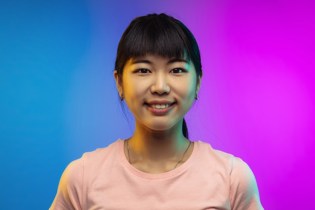 Smiling calm close up asian young womans portrait isolated on gradient in neon
