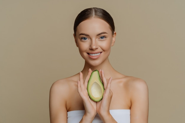 Smiling calm european woman with combed hair holds avocado as recommendation for nourishing face mask