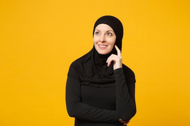 ヒジャーブの黒い服を着た穏やかな若いアラビアのイスラム教徒の女性の笑顔は、黄色の壁、肖像画で孤立して見上げて、手を組んで保持します。人々の宗教的なライフスタイルの概念。コピースペースのモックアップ