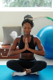 Улыбающаяся спокойная молодая темнокожая женщина сидит на коврике для йоги в позе лотоса и медитирует руками в жесте намасте