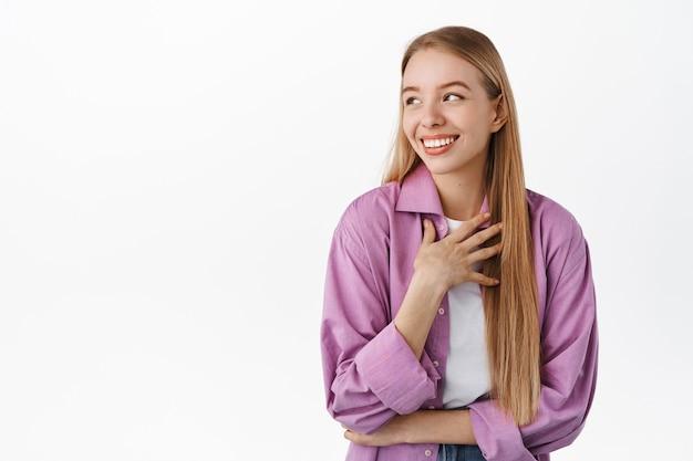 Sorridente ragazza candida, guardando da parte, ridendo con emozione naturale del viso felice, toccando il petto, ridacchiando per qualcosa di divertente, in piedi contro il muro bianco