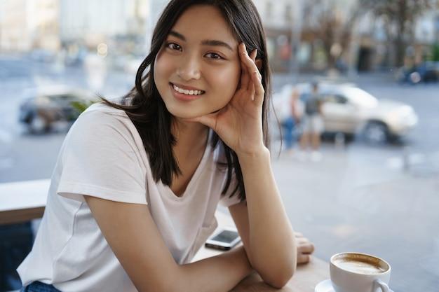 창 근처 카페에 앉아 커피를 마시는 동안 카메라에 행복을 찾고 웃는 솔직한 소녀. ㅏ
