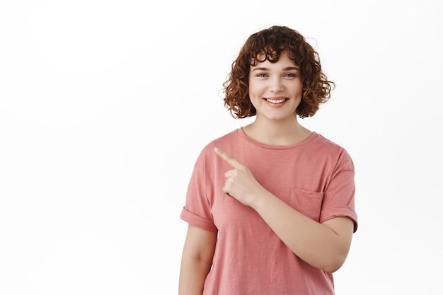 左の指を指している巻き毛の率直な女の子の笑顔、白のtシャツに立っているコピースペースを示しています