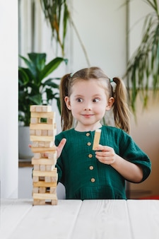 Smiling canny cute child in green dress looking at a wooden jenga tower standing on a table.