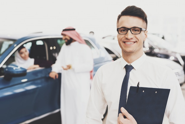 Smiling car dealer in auto salon vip arab clients.