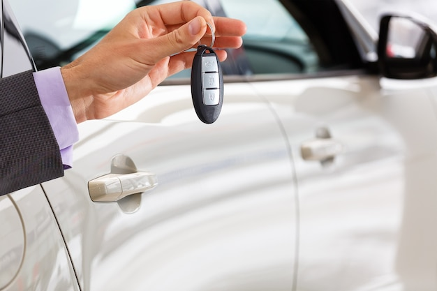 Улыбающийся продавец автомобилей передает ваши новые ключи от машины, концепцию представительства и продаж