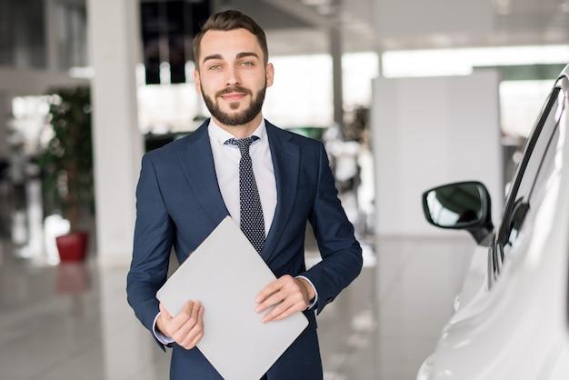 Smiling car salesman in showroom
