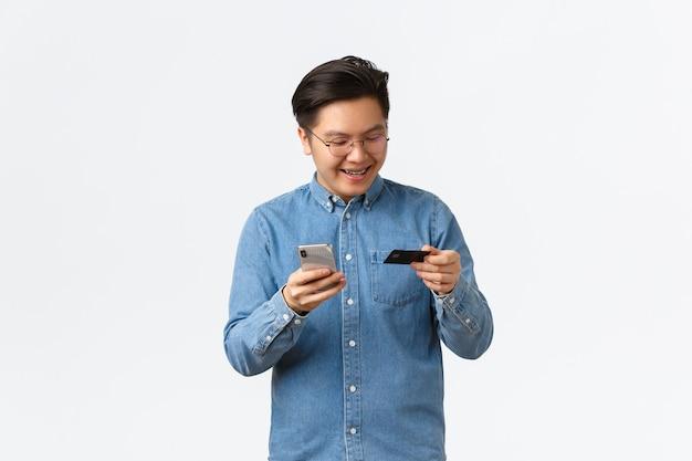 Sorridente uomo asiatico spensierato in occhiali e abiti casual, con bretelle, guardando la carta di credito soddisfatto, acquistando online con l'app per smartphone, facendo acquisti in internet con il telefono cellulare.